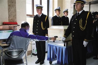 火化馆,工作人员扫描刚运送来的棺木上的二维码。