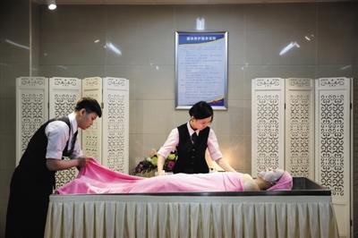 昨日,北京市八宝山殡仪馆首届公众开放日。殡仪服务人员正在通过模特演示遗体沐浴的过程。本版摄影/新京报记者 卢淑婵